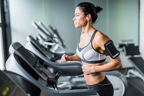 Fit Brunette Woman Running on Treadmill with Music