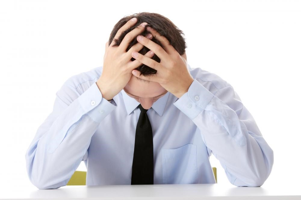 Man displaying frustration in front of a desk