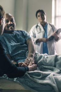 a-male-patient-smiles-while-holding-the-hand-of-a-friend