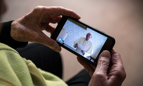 Worshiper participating in Pope Francis' eulogy using telecommuting