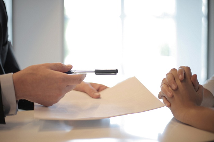 Man handing woman a pen to sign a contract